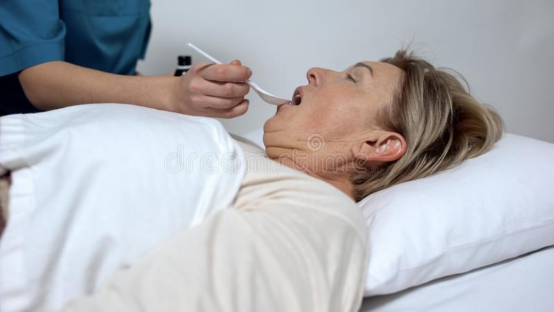 Hospice worker giving laxative syrup to disabled woman , treatment and therapy royalty free stock photos