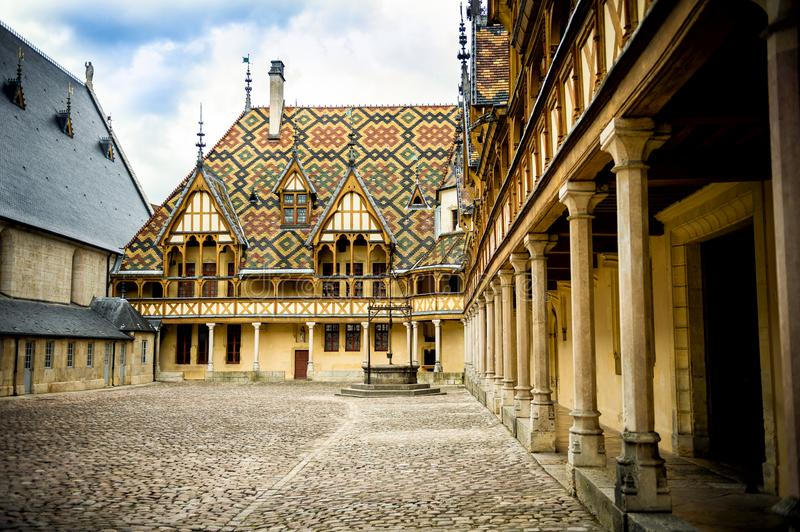 The Hospices of Beaune historic hospital, with visitors, in Beaune, Burgundy, France. The Hôtel-Dieu or Hospices de Beaune in Beaune is the city`s main stock photos