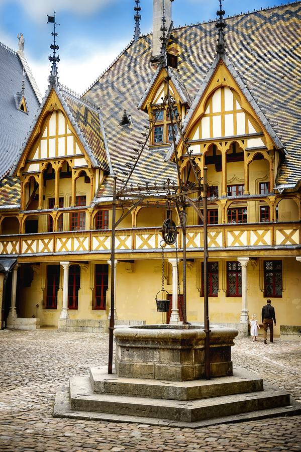 The Hospices of Beaune historic hospital, with visitors, in Beaune, Burgundy, France. The Hôtel-Dieu or Hospices de Beaune in Beaune is the city`s main stock photo