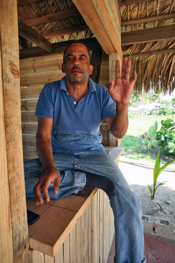 A hospitable man. Middle-aged man looking as Hispanic, of Dominican nationality, with a light stubble, gray hair, dressed in blue jeans and a blue t-shirt is royalty free stock photo