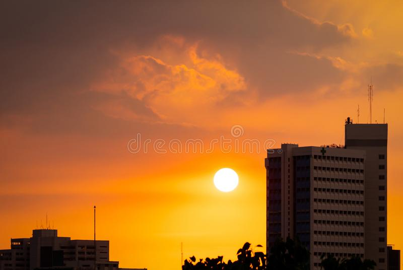 Hospital building at dusk with beautiful sunset sky. Silhouette of hospital building in the evening. Cityscape of skyscraper. Building. Big sun with golden sky royalty free stock image