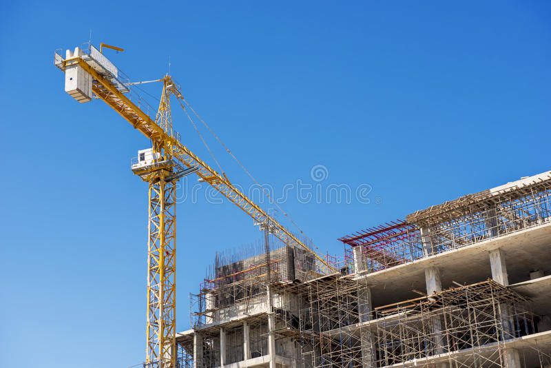 Hospital building under construction with cranes against a blue sky. Hospital building under construction with cranes against a blue sky royalty free stock images