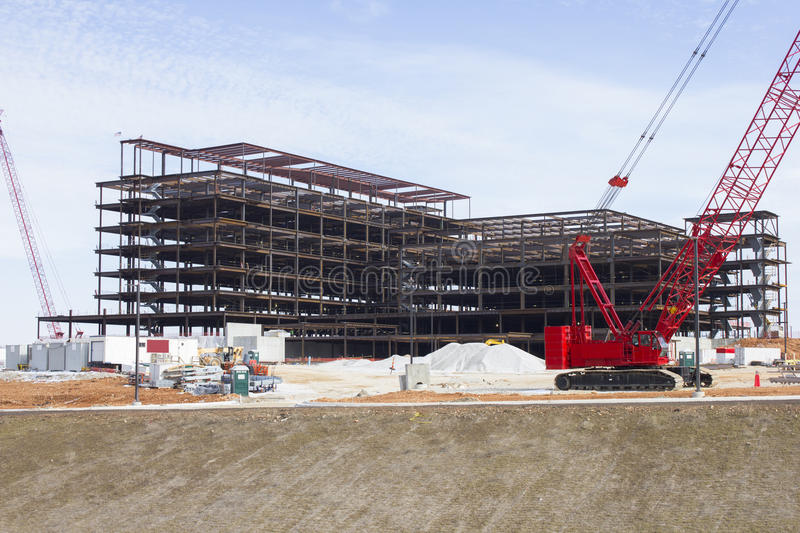 Hospital Construction Site & Crane. This image shows the steel framework of a large building under construction. The job site includes building materials, a stock images