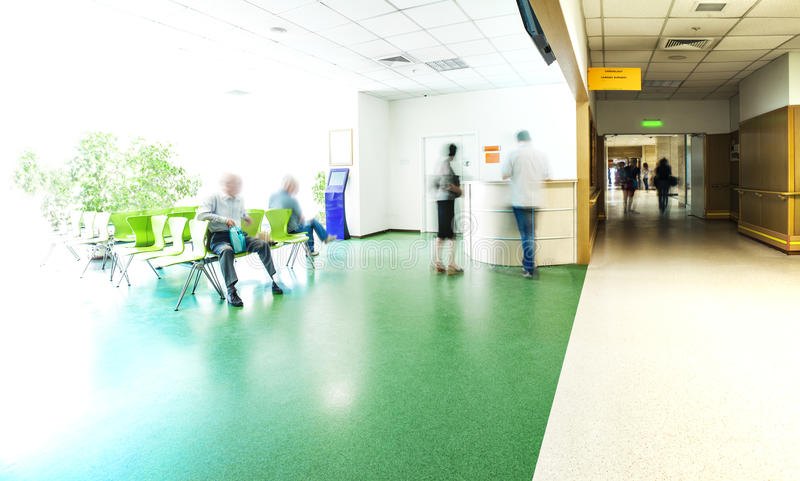 Hospital corridor reception. View of the registration desk, waiting area and a corridor in modern hospital with blurred figures of patients with a copy space royalty free stock photography