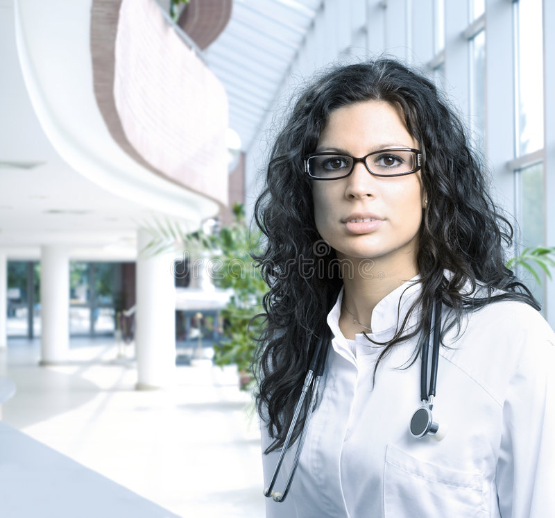 Hospital doctor. Young female doctor stands in the lobby of the hospital. Daylight, indoor royalty free stock photos