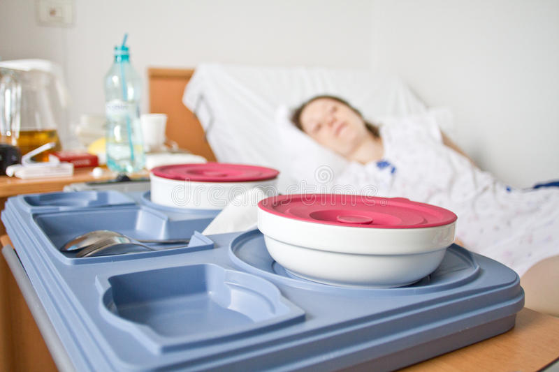 Hospital food. Tray with sick patient in background stock photography