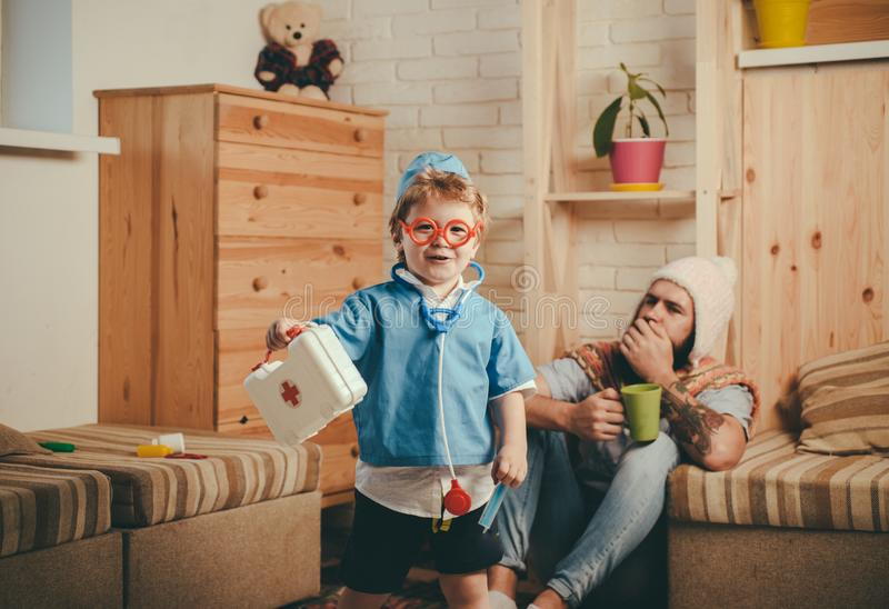 Hospital game, smiling boy dressed as doctor in red glasses holding first aid kit. Cute child with stethoscope playing stock photography