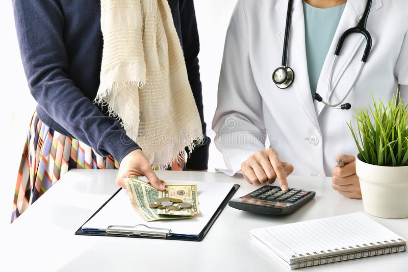 Hospital and medical expense, Doctor and woman patient calculate on disease treatment fee charges. stock photos