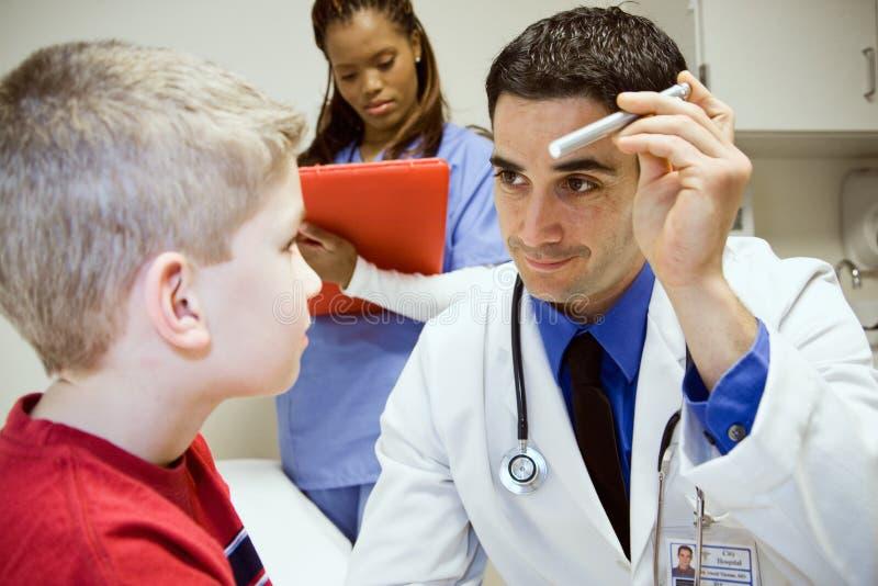 Hospital: Olhos amigáveis do ` s do doutor Looks At Boy imagens de stock royalty free