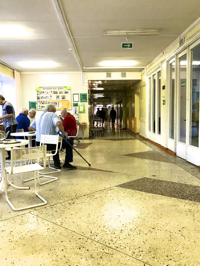 Hospital patients at lunch. They sit at the tables in the corridor of the clinic. stock image