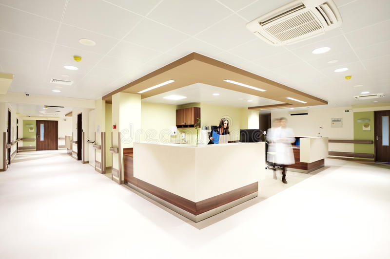 Hospital reception corridor. Reception in a modern hospital with a receptionist and a blurred doctor figure royalty free stock photo