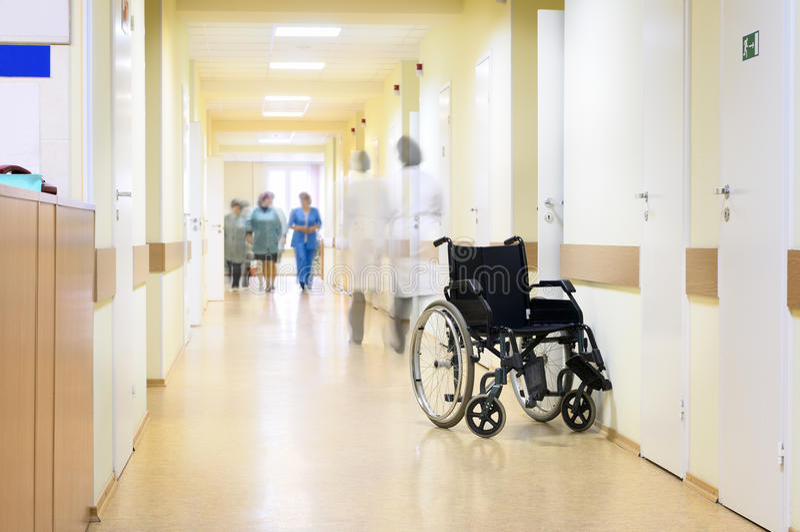 Hospital, sillón de ruedas y gente irreconocible. fotografía de archivo