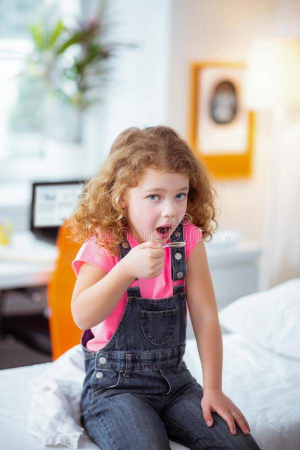 Stylish little girl sitting in the hospital and taking cough syrup stock image