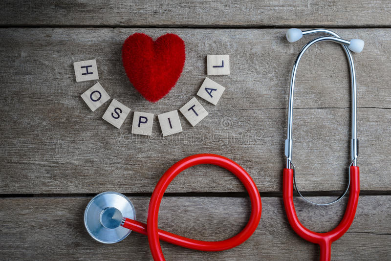 Hospital text word made with wood blocks and Red Heart,stethoscope on wooden table royalty free stock images