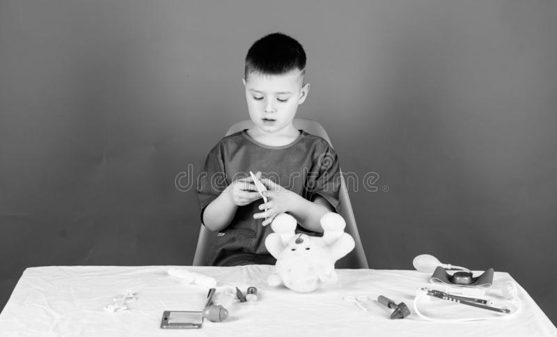 Hospital worker. Health care. Kid little doctor busy sit table with medical tools. Medical examination. Medicine concept royalty free stock photos