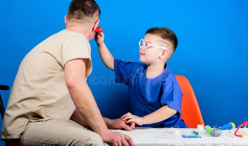 Hospital worker. Health care. Medicine concept. Kid little doctor sit table medical tools. Illness treatment. Dad and royalty free stock photos