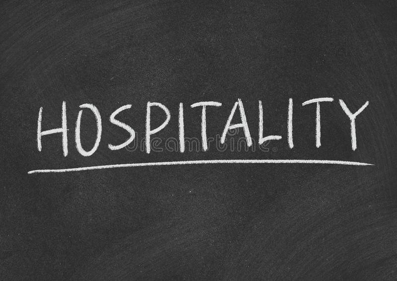 Hospitality. Concept word on a blackboard background stock photography