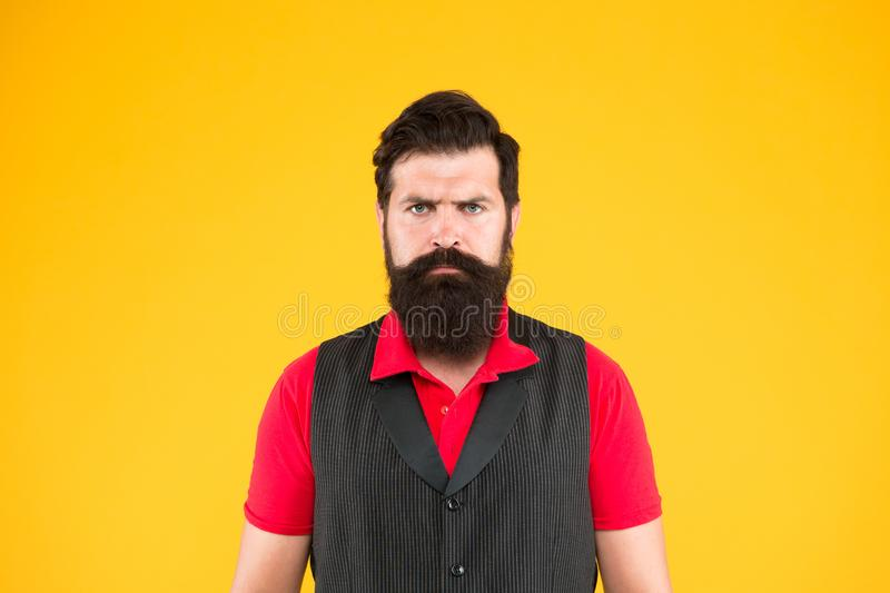 Hospitality staff. Restaurant cafe staff wanted. Man bearded hipster with mustache wear vest and shirt uniform yellow. Background. Shop staff concept. Salesman royalty free stock photography