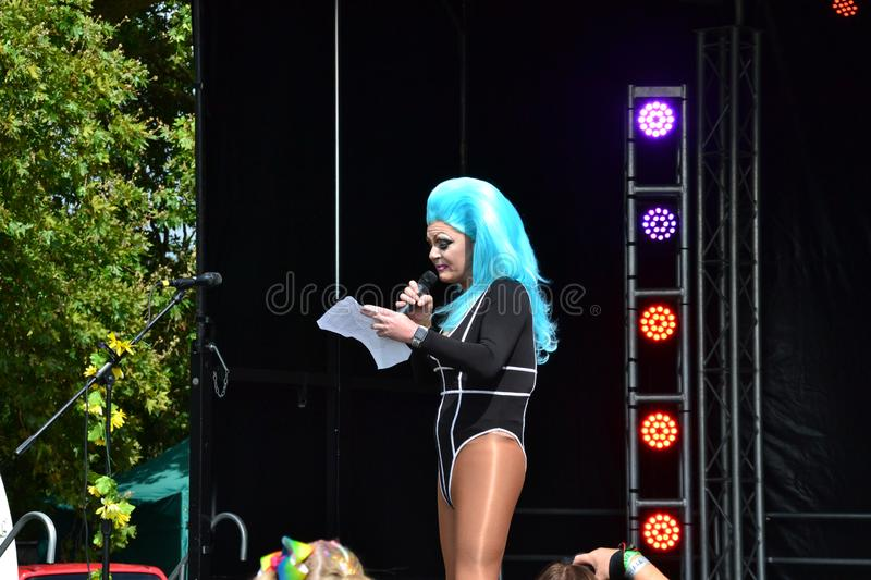 The host of the Reading Pride Parade 2019 holding a speech and opening the main stage. Reading, Berkshire, UK, England, 31st August 2019, People celebrating stock image