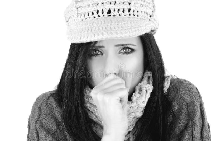 Hosta för kvinna som är sjukt i den svartvita vintern royaltyfri fotografi