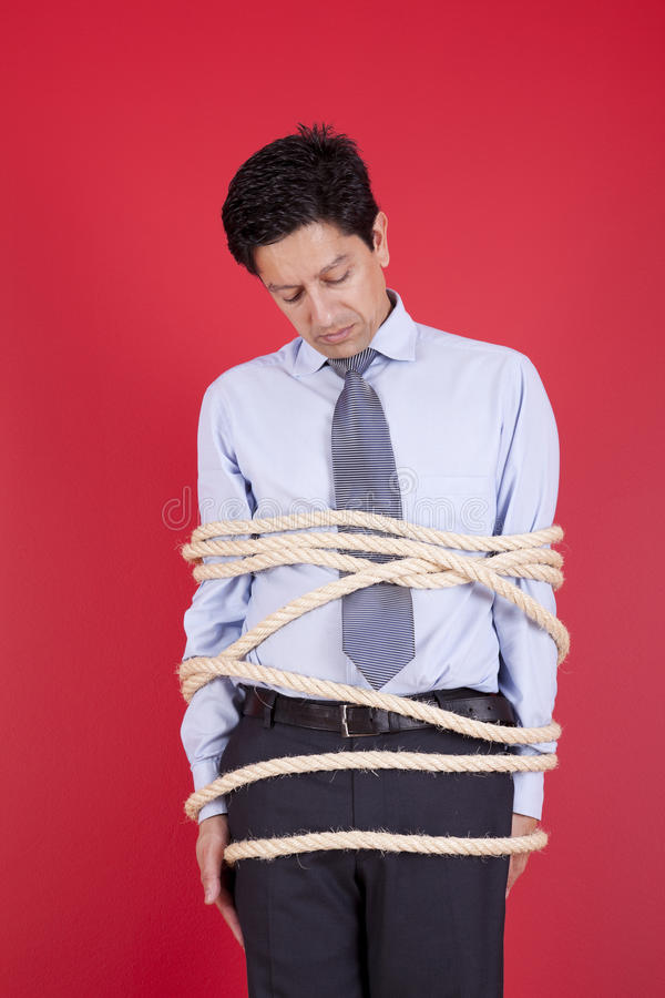 Hostage businessman. Businessman tied up with a rope struggle to get free stock photo