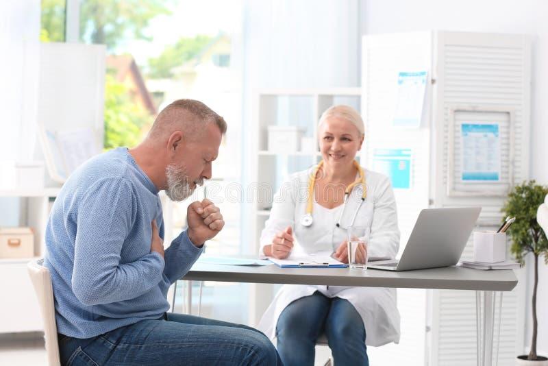 Hostande mogen man som besöker doktorn arkivbild