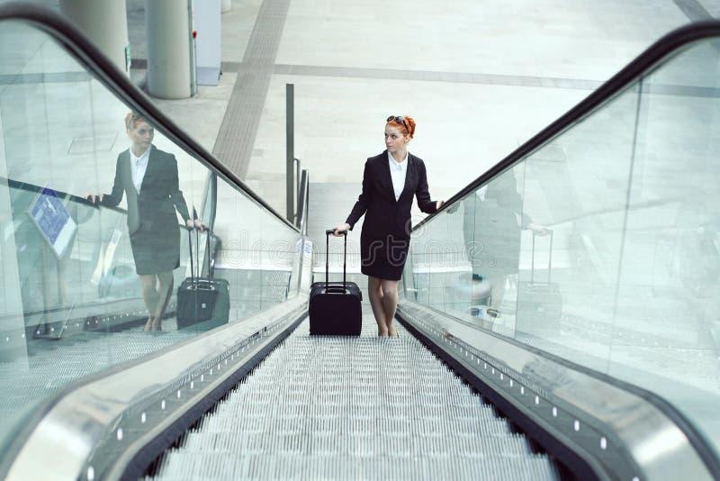 Hosteß auf Rolltreppe im Flughafen lizenzfreies stockfoto