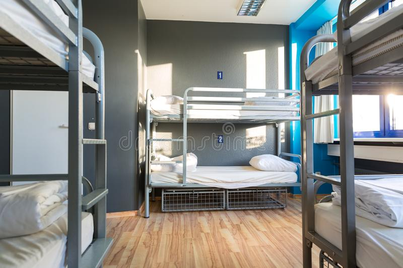 Hostel interior, metal bunk beds and linen, nobody stock photo