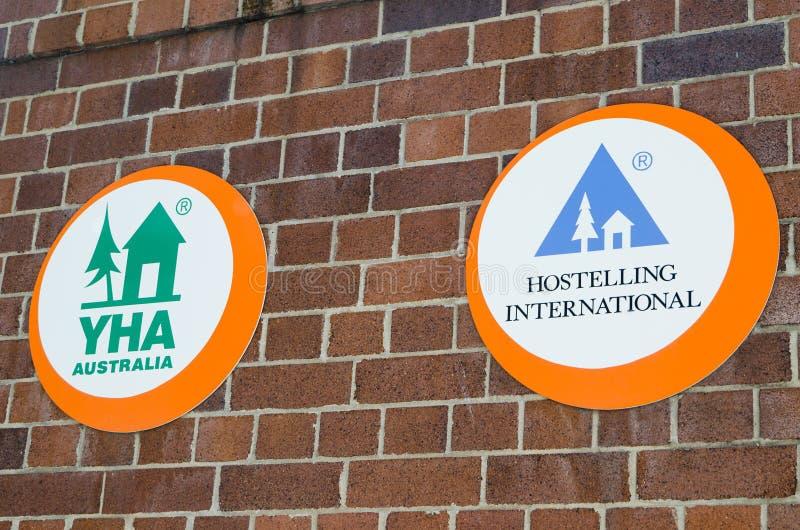 Hostelling anslutning för YHA-ungdom och Hostelling internationella logoer på väggen för röd tegelsten royaltyfri fotografi