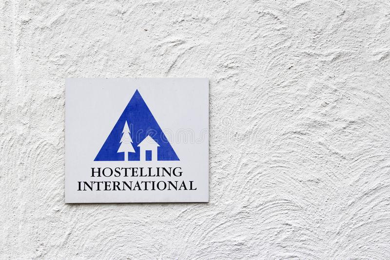 Hostelling internationellt tecken på den vita väggen royaltyfria bilder