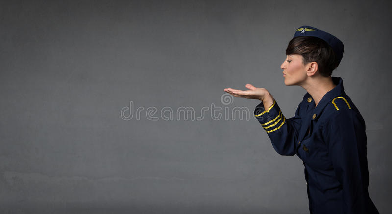 Hostess blowing kisses with open hand. Dark background royalty free stock image