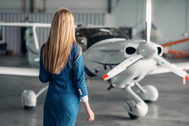 Hostess contro l'aeroplano del turbopropulsore in capannone immagine stock