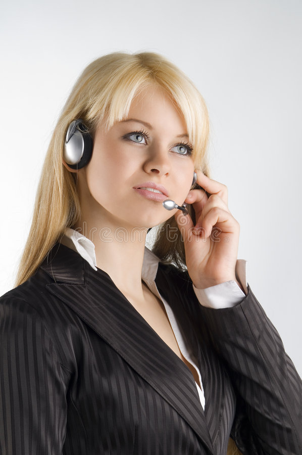Hostess with earphone. Cute blond girl with earphone and formal dress royalty free stock photography