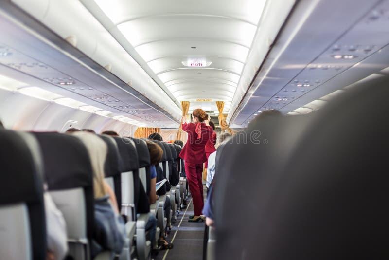 Hostess nelle istruzioni di sicurezza danti uniformi di rosso sull'aeroplano commerciale dei passeggeri immagini stock