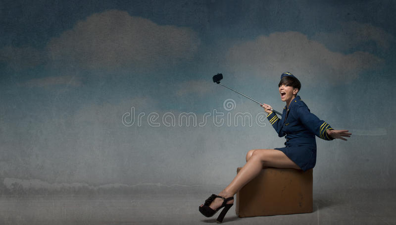 Hostess take selfie with camera phone. Textured sky royalty free stock image