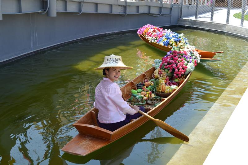 Hostess of the Thailand pavilion of the EXPO Milano 2015 is sitting in a traditional Thai wooden boat filled with heap of flowers. stock images