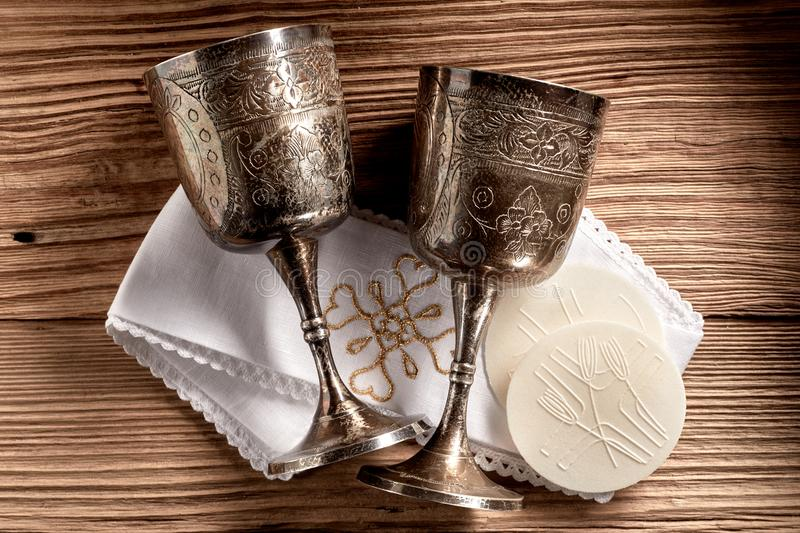 Hostie wafers with silver chalice cups and cloth. Ready for the Holy Communion service in a church on rustic wood background stock images