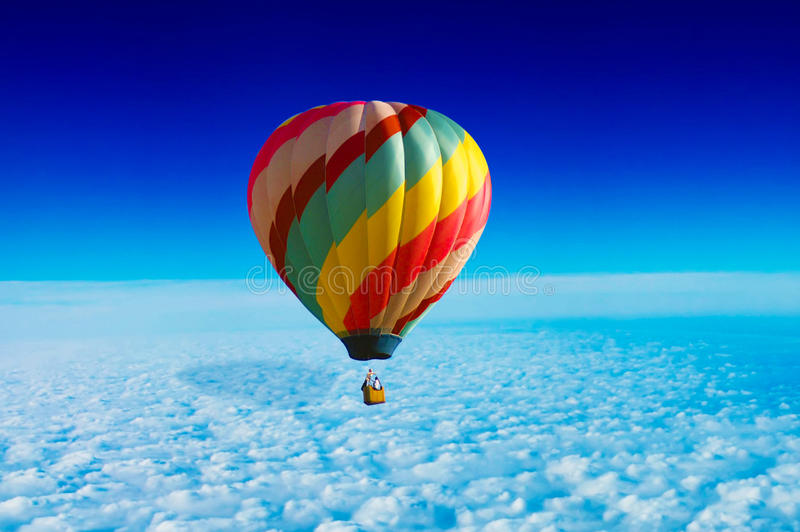 Hot Air Balloon. A hot air balloon above the clouds, under the clear blue sky royalty free stock photos