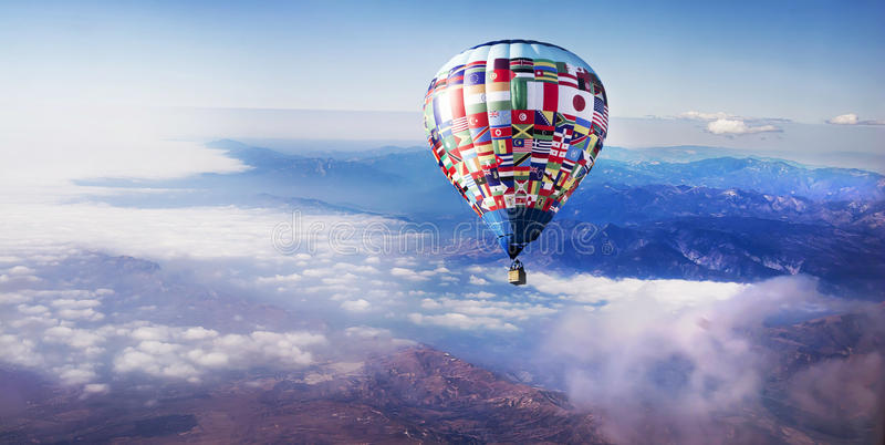 Hot Air Balloon Above Clouds. A hot air balloon with flags of the world drifting amongst soft clouds in early morning light royalty free stock images