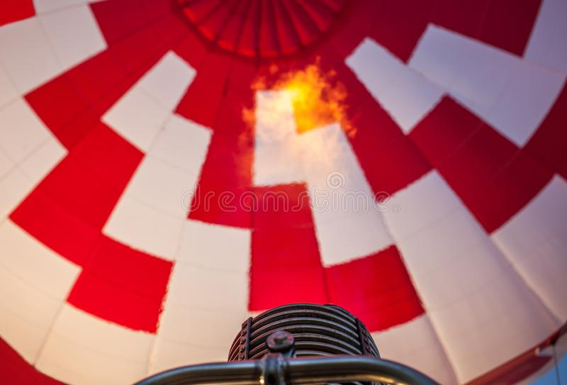 Hot air balloon or aerostat, bright burning fire flame from gas burner equipment. Close up from inside, short focus royalty free stock photo