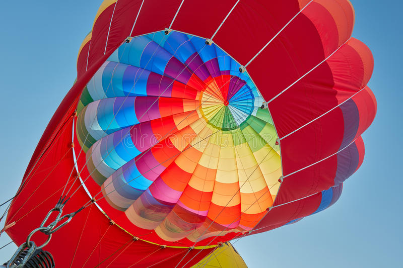 Hot air balloon, colorful aerostat inflating, blue sky. Hot air balloon, colorful aerostat inflating in a clear sunny day, blue sky royalty free stock images