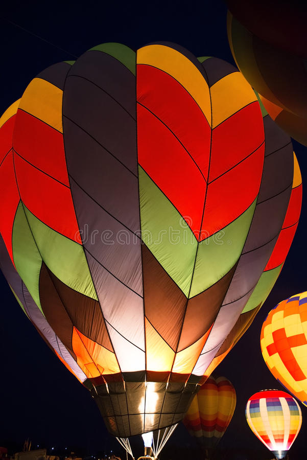 Hot Air Balloon Evening Glow Color Light Show. Hot air balloons glow in an evening light show as the balloon pilots fire them up in a bright display of color stock photos
