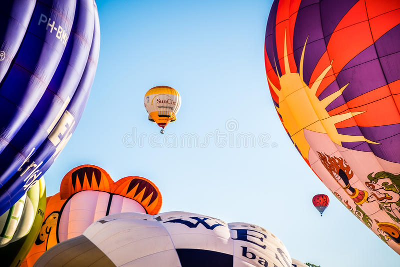 Hot air balloon festival, Barneveld, Netherlands. Close up of hot air balloons inflating and flying at festival in Barneveld, Netherlands against blue skies on stock photos