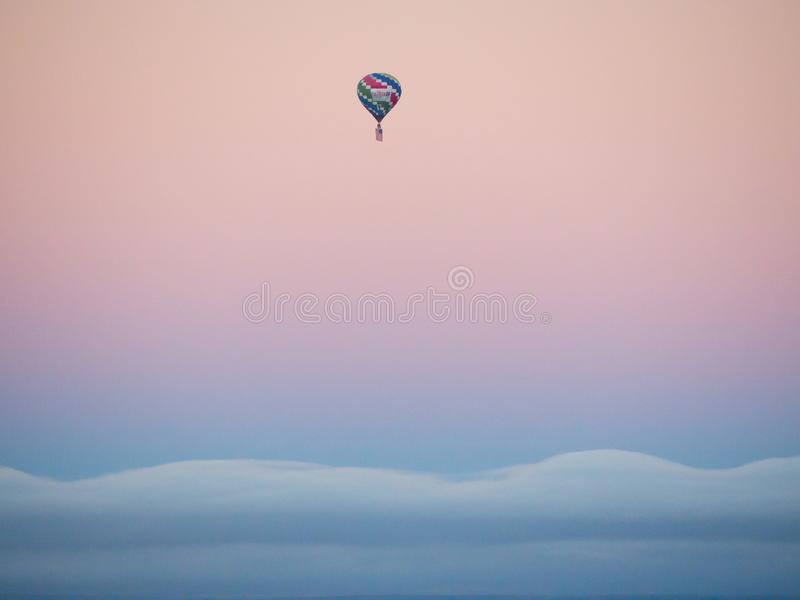 Hot air balloon, flying the American Flag at sunrise. 2019 Albuquerque International Balloon Fiesta. A hot air balloon flies over Albuquerque at sunrise, with royalty free stock photos