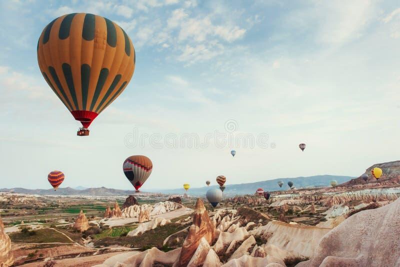 Hot air balloon flying over rock landscape at Cappadocia Turkey. royalty free stock image