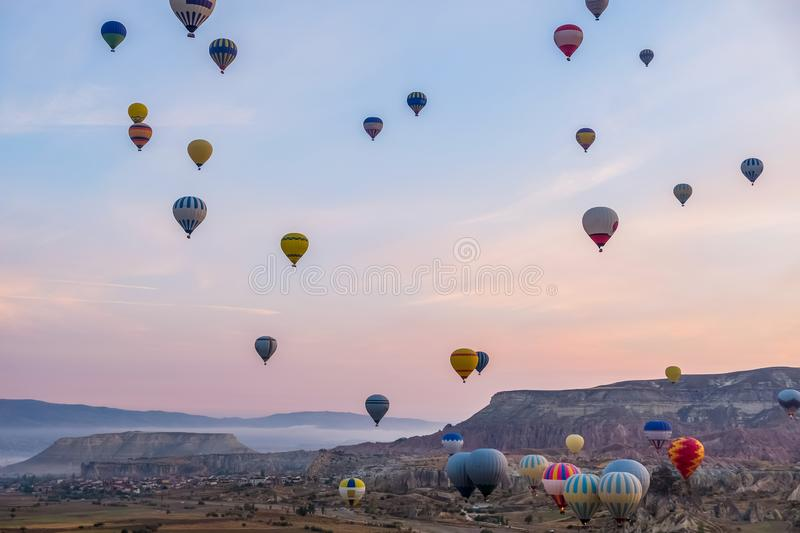 Hot air balloon flying over spectacular Cappadocia, Tourists enjoy the overwhelming views over Cappadocia, Turkey royalty free stock photography