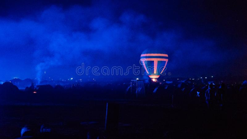 Hot air balloon flying over spectacular Cappadocia under the sky with milky way and shininng star at night with grain stock photography