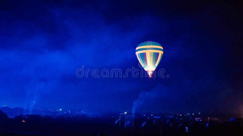 Hot air balloon flying over spectacular Cappadocia under the sky with milky way and shininng star at night with grain stock images