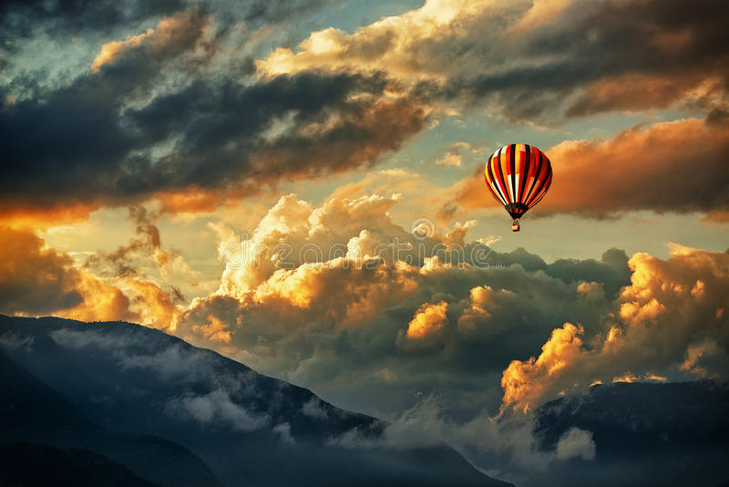 Hot air balloon. Flying in a sky full of clouds at sunset stock photo