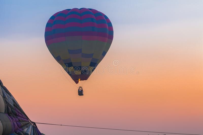 Hot air balloon flying in the sky at sunrise. Chiang Rai,Thailand - February 18,2018:hot air balloon flying above Singha park in Chiangrai Thailand. balloons royalty free stock photography